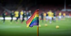 Players warm up behind a rainbow corner flag