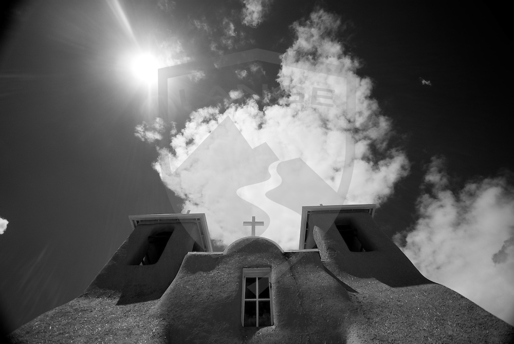 the san francisco de assisi church in taos new mexico is a 1700s era adobe church and is a famous international landmark.  its unique lines intersecting with the singing new mexico sun creates abstract impressions of architecture and religion.