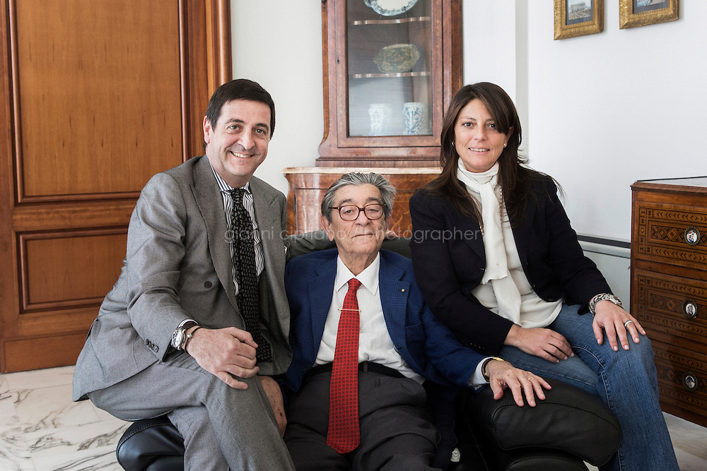 ARZANO, ITALY - 10 APRIL 2014: (L-R) CEO Antonio De Matteis, Founder and President Ciro Paone and Vice President and General Manager Maria Giovanna Paone, pose for a family portrait at the Kiton headquarters and factory in Arzano, Italy, on April 16th 2014.<br /> <br /> Kiton is a luxury clothing company co-founded in 1956  in Naples by Ciro Paone, a fifth-generation fabric merchant. Launched in 1968, the brand produces suits, overcoats, ties, shirts, trousers, knitwear, outwear, shoes, leather accessories, and bags,  womenswear, fragrances and eyewear. Kiton produces 22,000 men suits per year and their sales proceeds was of 95mln euros.