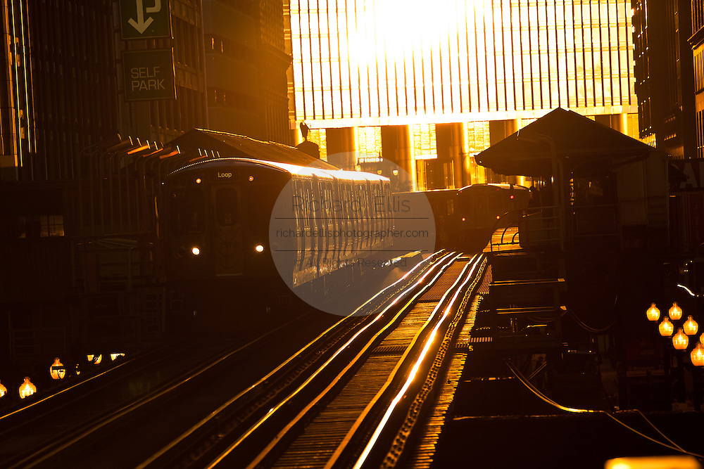 "Sunrise illuminates the elevated tracks of the Chicago rapid transit system known as the""L""  in Chicago, IL, USA."