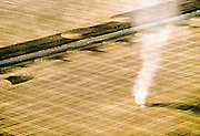 A dust devil, a rotating updraft of wind, picks up soil on recently tilled agricultural land. The dust gives form to air currents that would otherwise be invisible.