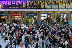 © Licensed to London News Pictures. 20/07/2018. London, UK. Hundreds of people wait for train information at London Kings Cross station on 'frantic Friday' as thousands of holidaymakers head off at the start of the school holidays. Photo credit: Rob Pinney/LNP