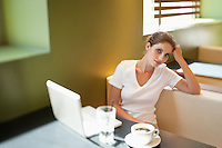Portrait of young woman sitting at table with laptop in cafe