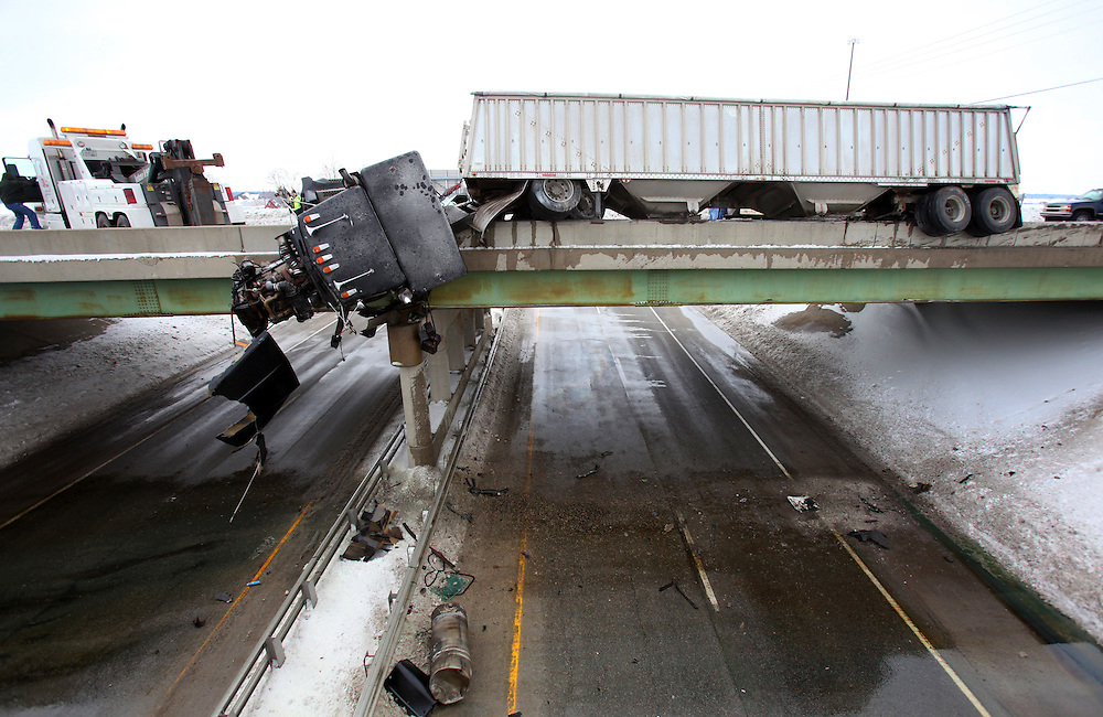 A semi truck hangs off a bridge on Ind. 67 and the Muncie bypass Wednesday afternoon just outside Muncie, Ind. A truck hit a car sending the truck dangling over the side of a bridge. One person in the car later died. The driver of the semi climbed out of the cab and was uninjured.