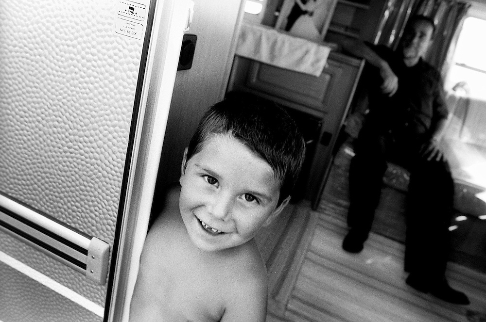 "Child with his father in their caravan. France, Marville, August 2002 - 40,000 Gypsies from all over the Europe come together and pray in Marville, a little village in France. They encamped in a former air base of NATO during 1 week. ""Vie et Lumiere"" is an International Evangelic Community.©Jean-Michel Clajot / Cosmos"
