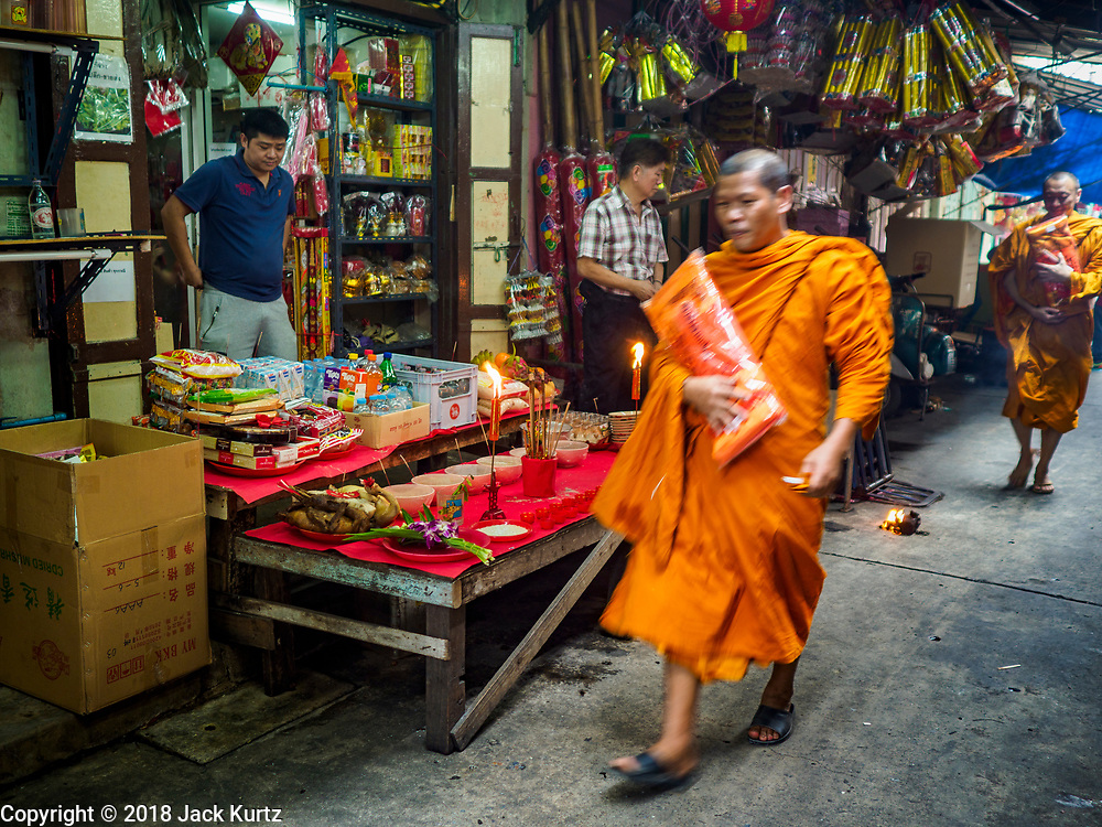 15 FEBRUARY 2018 - BANGKOK, THAILAND: Buddhist monks walk past homes with Tet altars in front of them in a small alley in Bangkok's Chinatown. Lunar New Year, also called Tet or Chinese New Year, is 16 February this year. The coming year will be the Year of the Dog. Thailand has a large Chinese community and Lunar New Year is widely celebrated in Thailand, especially in Bangkok and large cities with significant Chinese communities.    PHOTO BY JACK KURTZ