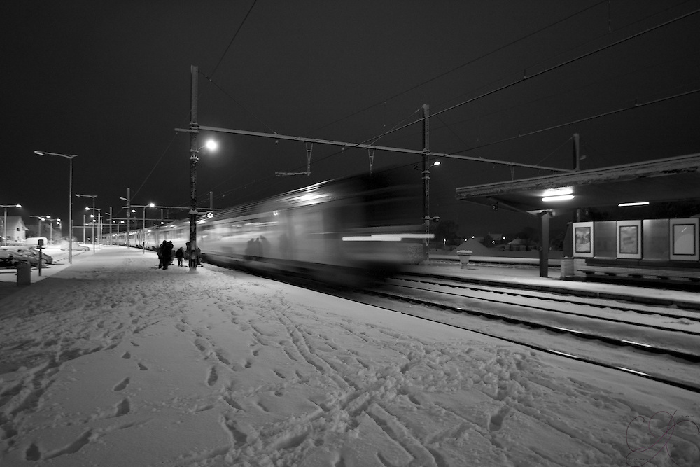 Night train moves down the tracks as it pulls away from the Jurbise station on a cold winter's night