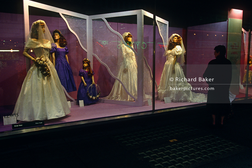 Bridal wedding dresses are watched by shopper on shop window mannequins in London's John Lewis department store.