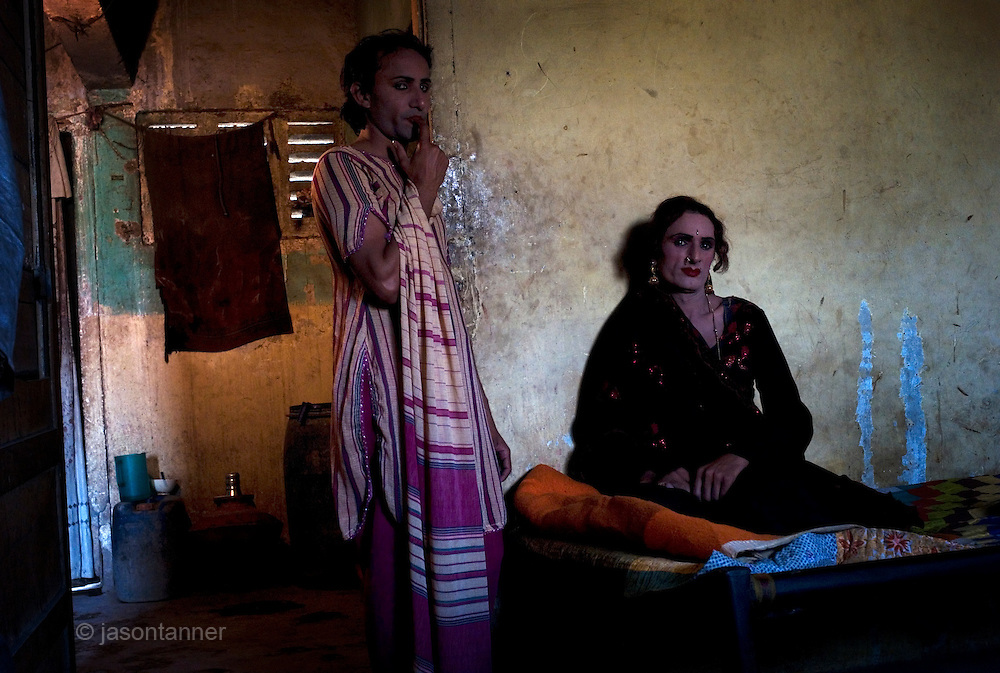 Reema, a 35 year old Hijra (sitting) and Sonya rest before leaving for the evenings work on the streets of Karachi...The word Hijra is an Urdu word meaning eunuch or hermaphrodite. However, most Hijras in Pakistan are gay men who leave home to join the Hijra community as young boys where there is more acceptance. Most identify themselves as more feminine then masculine and dress and act accordingly...Although tolerated in a country where homosexuality is against the law, Hijras are largely ostracised from society. They are often denied work opportunities, rejected by most families, lack formal education and live in poorer areas of the city...They share similarities with the more famous Hijra communities in the Indian subcontinent and Bangladesh. In a continent where great emphasis is placed on one's ability to have children, those who are unfortunate not to be able to conceive children are not considered a true man or woman. Life for many Hijras in Pakistan consists of begging for alms (Zakat) in the more prosperous areas of the city as well as slums in addition to receiving alms when bestowing blessings on male babies and at weddings....Most Hijras dress as women, and engage in activities such as dancing and entertaining in public - activities that would be considered inappropriate for women of the subcontinent. Some members of the community engage in prostitution. .