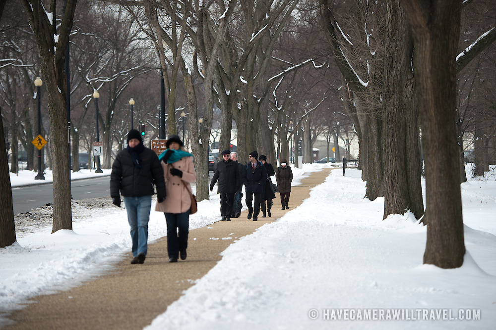 Tourists walk along a cleared path along Independence Avenue in Washington DC after a snow storm.