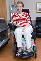 Older woman wheelchair user using a TV remote control,