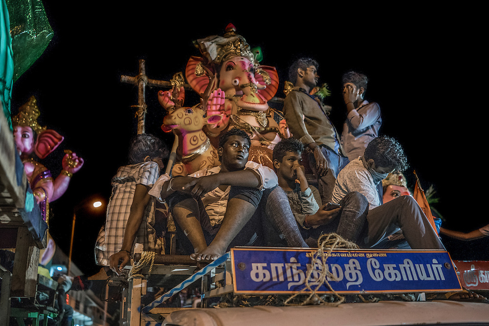 Local village men sit on the roof of a truck with a large Ganesha statue in the back during the Ganesha Chaturthi Festival in Pondicherry, India.