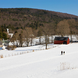 A couple walks through a snowy field at the Tyringham Cobble Reservation in Tyringham, Massachusetts.  Berkshire Mountains. The Trustees of Reservations.