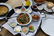 Traditional Israeli Breakfast with omelet, cheeses, salads, a fresh roll and a cup of cappuccino