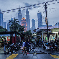 A busy Kampung Baru street scene after rain against the backdrop of iconic Petronas Towers in Kuala Lumpur, Malaysia, 12 April 2017.