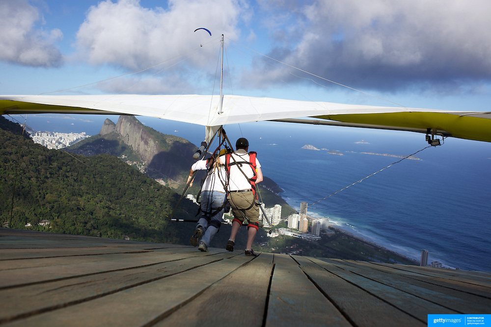 A tandem hang glider prepares to take off above the hillside of Pedro Bonita high in the hills of Rio de Janeiro. Pilots of hang gliders and para gliders take tourists for tandem flights with breathtaking views of the city before landing on Sao Conrado beach. Rio de Janeiro,  Brazil. 9th September 2010. Photo Tim Clayton