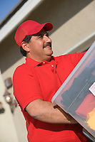 Close-up view of middle-aged delivery man unloading containers