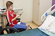 30 DECEMBER 2009 -- PHOENIX, AZ:  Mackenzie Saunders (CQ) uses a cell phone to text message a friend while she waits for her bed to be made at St. Joseph's Hospital in Phoenix Wednesday. Mackenzie was knocked down by another player during a soccer game. She finished the game but later in the day her legs started hurting and her parents took her to a hospital. Three hospitals later, she was in St. Joseph's with a diagnosis of a swollen spine and she couldn't walk. Now she's in physical therapy. She is expected to make a full recovery but her doctors have said she won't be able to play soccer for at least another 16 months. Photo by Jack Kurtz
