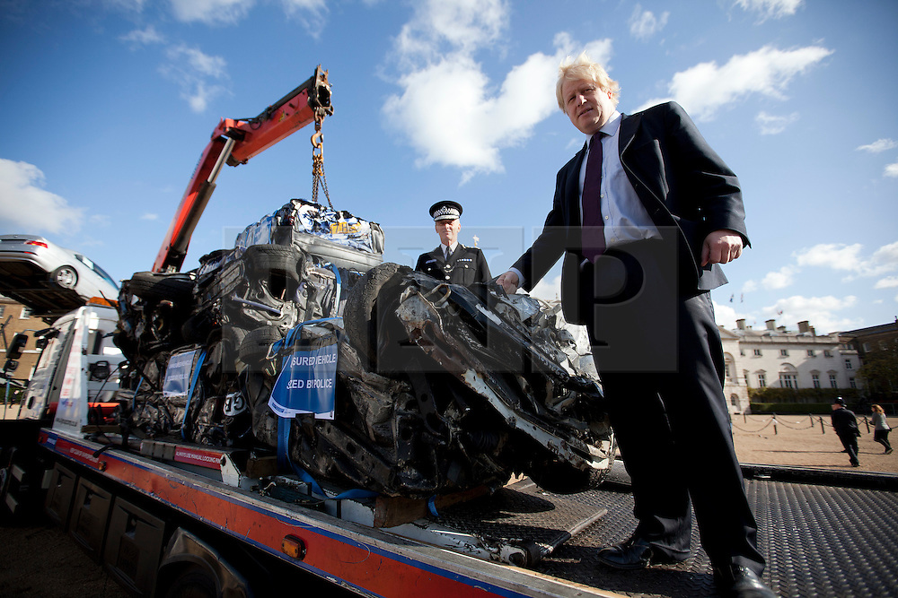 © Licensed to London News Pictures. 19/10/2011. LONDON, UK. The Mayor of London, Boris Johnson,  and the Metropolitan Police Commissioner, Bernard Hogan-Howe, stand next to a pile of crushed cars on Horse Guards Parade in London today (19/10/11). The cars were all seized as part of 'Operation Reclaim', a coordinated Metropolitan Police operation across the capital cracking down on uninsured drivers. Photo credit: Matt Cetti-Roberts/LNP