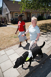 Woman with visual impairment with friend walking down street with guide dog.