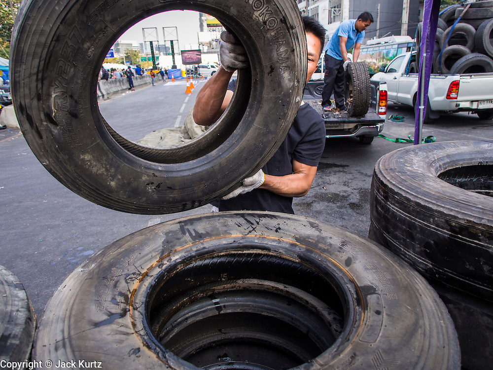 17 JANUARY 2014 - BANGKOK, THAILAND: Anti-government protestors build bunkers out of old tires at a protest site in the Lat Phrao intersection in Bangkok. Friday was day 5 of the anti-government Shutdown Bangkok protests. The protest, led by the People's Democratic Reform Committee, is calling for the suspension of elections pending political reform in Thailand. There was violence at several sites in Bangkok Friday, including running battles between government opponents and supporters at one site and an IED attack by unknown assailants on anti-government protestors at another site.    PHOTO BY JACK KURTZ