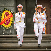 Two soldiers goosestep their way from the entrance of the Ho Chi Minh Mausoleum as part of the changing of the guard ceremony. A large memorial in downtown Hanoi surrounded by Ba Dinh Square, the Ho Chi Minh Mausoleum houses the embalmed body of former Vietnamese leader and founding president Ho Chi Minh.