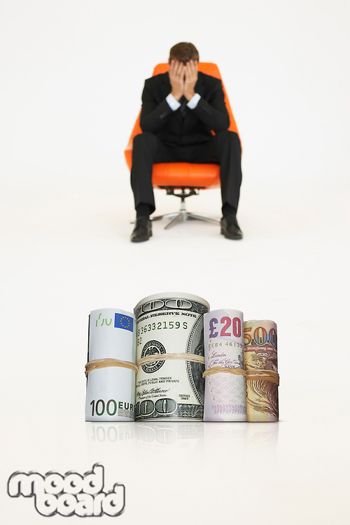 Money rolls with worried businessman on chair representing financial problems