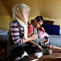 Syrian refugee Nazma Abdul Baki, 18-years-old, looks after her disabled brother Ahmed Abdul Baki, 12-years-old, inside the tent they share with 7 other people at the Domiz camp outside of Dohuk in Iraqi Kurdistan, Wednesday, August 28, 2013. The family from Qamishli fled Syria 7 months ago to escape the hostilities and the economic problems in the country.  August 2013.