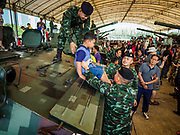 """13 JANUARY 2018 - BANGKOK, THAILAND:        Thai soldiers help a child jump off a Type 85 armored personal carrier during Children's Day activities at the Royal Thai Army's King's Guard 2nd Cavalry Camp in central Bangkok. Children's Day is called """"Wan Dek"""" in Thai. Many government offices and military bases hold special activities for children as do shopping malls. Thailand purchased the type 85 from China.   PHOTO BY JACK KURTZ"""