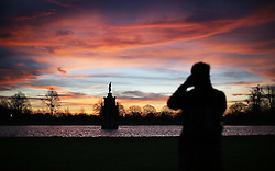 © Licensed to London News Pictures. 28/12/2015. London, UK.  A cyclist takes photographs as the sun rises over the Diana Fountain in Bushy Park. Photo credit: Peter Macdiarmid/LNP