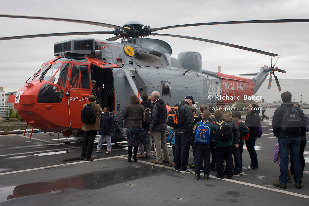 Visitors admire a Sea King helicopter while touring the top deck on-board the Royal Navy's aircraft carrier HMS Illustrious during a public open-day in Greenwich. Illustrious docked on the river Thames, allowing the tax-paying public to tour its decks before its forthcoming decommisioning. Navy personnel helped with the PR event over the May weekend, historically the home of Britain's naval fleet.