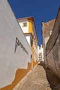 Residential buildings in cobbled alley with historic whitewashed houses. An image of life one of the old neighbourhoods in the city centre of Evora, Alto Alentejo, Portugal, southern Europe