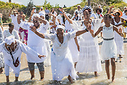 Descendants of enslaved Africans brought to Charleston in the Middle Passage dance to honor their relatives lost during a remembrance ceremony along the ocean front June 10, 2017 in Sullivan's Island, South Carolina. The Middle Passage refers to the triangular trade in which millions of Africans were shipped to the New World as part of the Atlantic slave trade. An estimated 15% of the Africans died at sea and considerably more in the process of capturing and transporting. The total number of African deaths directly attributable to the Middle Passage voyage is estimated at up to two million African deaths.