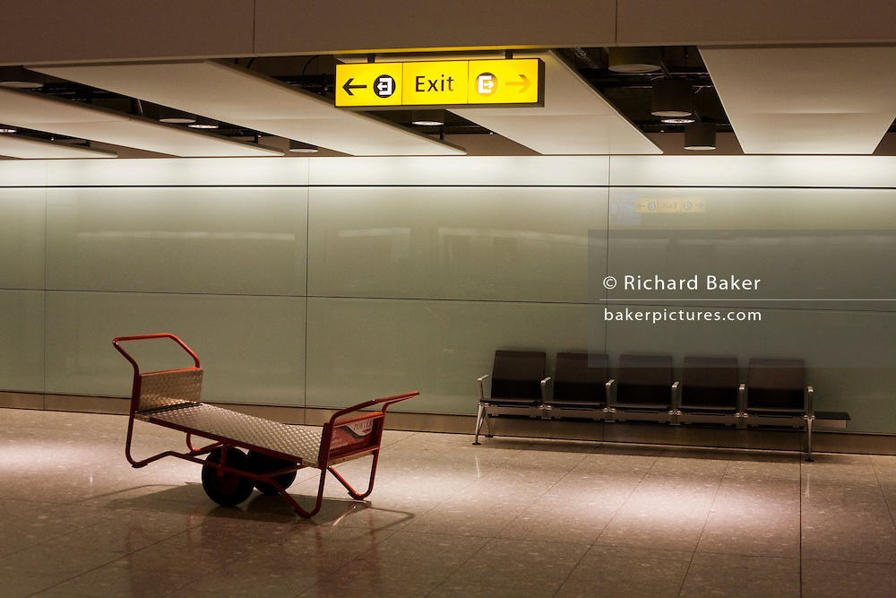 International baggage reclaim hall seating and Skycap luggage barrow at Heathrow's Terminal 5. .