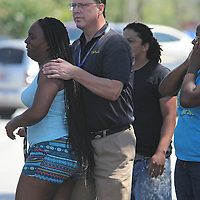 A chaplain comforts a woman who cried out Friday morning as an ambulance carried away a man suspected of shooting his girlfriend before he was found unresponsive at the end of a nearly three-hour standoff on West Montague Avenue in the North Charleston area. (ANDREW KNAPP/STAFF)