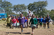Children racing each other outdoors with Mercy the teacher standing by. The MADICAA school (makadara division campaign against aids) in Makadara, Kenya, a Pre-primary/nursery school that started in 2006.