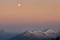 Fulll moon setting at dawn above the Coast Mountains of Britisg Columbia Canada