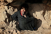Hamidah, 6, is sitting alone next to a cave dug out of the friable the cliff where once stood the two giant Buddhas of Bamyan during the late afternoon hours when the Sun is setting on the Hindu Kush mountain range, in Bamyan, central Afghanistan, an area mostly populated by Hazaras. A historically persecuted minority (15%) due to more lenient Islamic faith and characteristic 'Eastern' lineaments, Hazaras constitute the 70% of Bamyan's population.