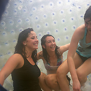 Participants inside a Zorb Globe preparing for a zorb ride down hill. The sport of Zorb globe riding was invented in New Zealand and globes are designed, manufactured and tested there, The Zorb globe is an 11 foot high inflatable transparent sphere which you can ride inside. Two feet of air protect participants from the ground enabling you to globe ride down hills at high speed.  Agrodome, Western Road. Ngongotahaha.  Rotorua, New Zealand,, 11th December 2010 Photo Tim Clayton.