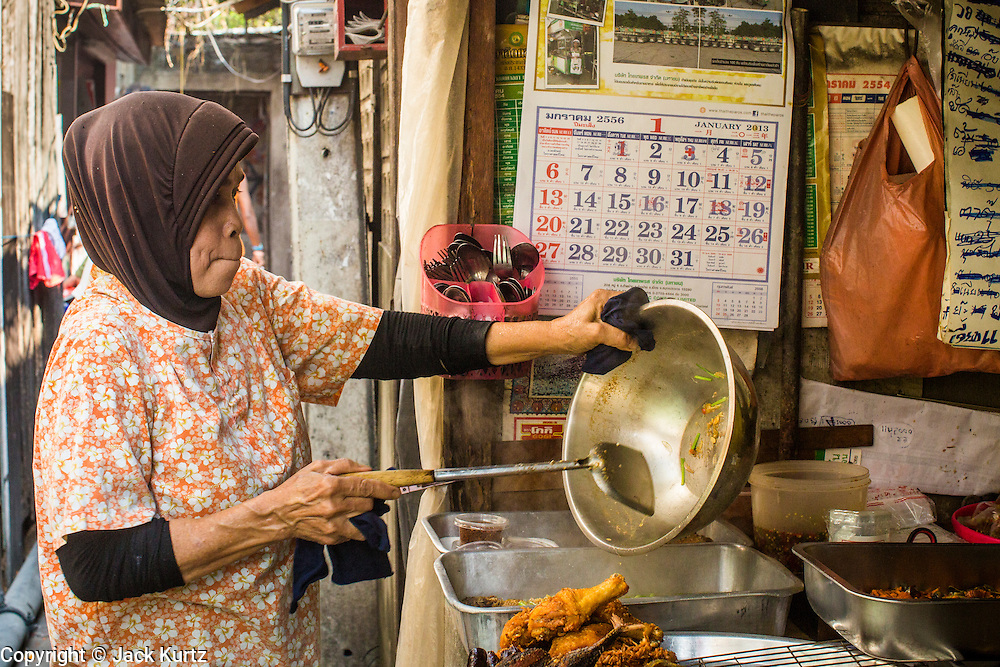 "10 JANUARY 2013 - BANGKOK, THAILAND:  A Muslim woman prepares food at the lunch stand in front of her home in the Baan Krua neighborhood in Bangkok. The Ban Krua neighborhood of Bangkok is the oldest Muslim community in Bangkok. Ban Krua was originally settled by Cham Muslims from Cambodia and Vietnam who fought on the side of the Thai King Rama I. They were given a royal grant of land east of what was then the Thai capitol at the end of the 18th century in return for their military service. The Cham Muslims were originally weavers and what is known as ""Thai Silk"" was developed by the people in Ban Krua. Several families in the neighborhood still weave in their homes.   PHOTO BY JACK KURTZ"