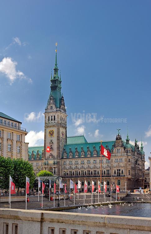 Das Rathaus mit kleiner Alster im Herbst bei sonnigem Wetter. Alles ist beflaggt mit der Hamburg Fahne.