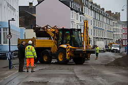 © London News Pictures. Aberystwyth. UK08/01/2014. <br /> The clean up operation continues  in Aberystwyth after days of stormy weather severely damaged the promenade.  The local authority has closed off the area  to enable the work to proceed safely, allowing the use of heavy machinery to clear the hundreds of tons of rubble left on the seafront. Photo credit: Keith Morris/LNP