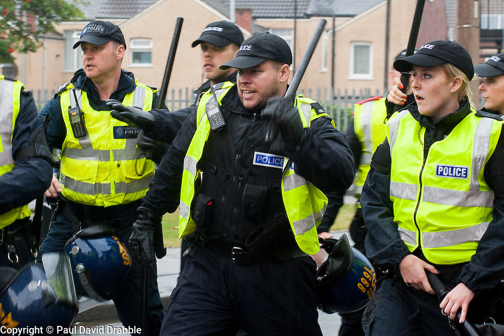 South Yorkshire PSU officers with battons drawn prepare to face UAF anti EDL protesters on a side street in Hexthorpe Doncaster South Yorkshire on Saturday Afternoon.<br /> The EDL and UAF are thought to have chosen Hexthorpe after recent media reports of tension between newly arrived Roma residents and the the local community<br /> 19 July 2014<br /> Image © Paul David Drabble <br /> www.pauldaviddrabble.co.uk