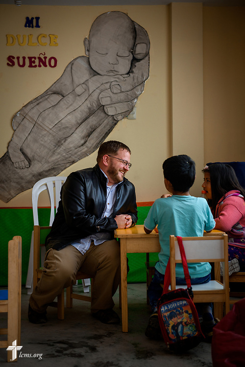 """The Rev. Eddie Hosch, LCMS career missionary to Peru, sits with children at Castillo Fuerte on Monday, Nov. 6, 2017, in the Chorrillos area of Lima, Peru. On the wall reads """"My Sweet Dream."""" LCMS Communications/Erik M. Lunsford"""