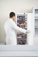 Scientist looking in refrigerator of specimens in laboratory
