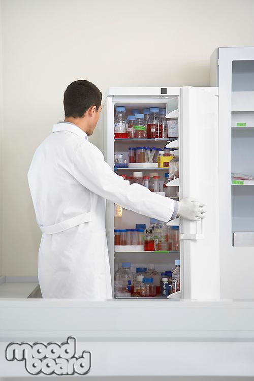 Scientist looking in refrigerator of specimens in laboratory