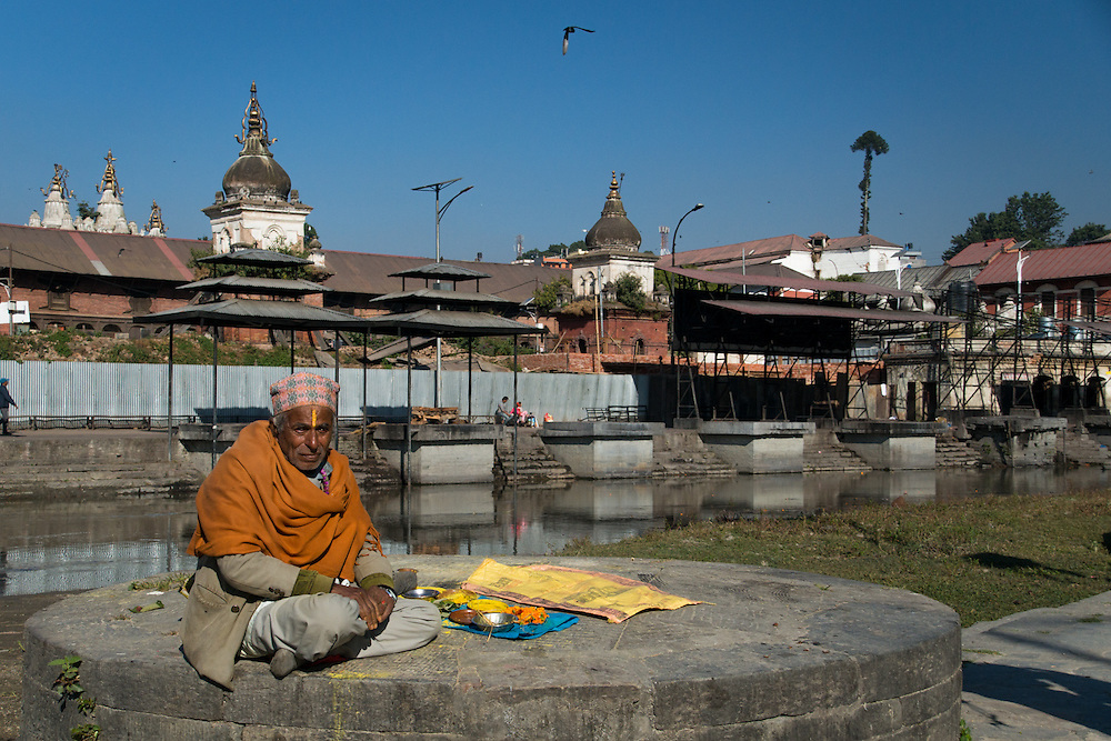 We were taking a walk by the Bagmati River in Nepal when we saw several pandits sitting by the river with colorful sand and rice.  This image was captured before he sat down a client to read into their future and help them deflect the potentials of sorrows and sadness.
