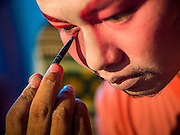 "06 DECEMBER 2015 - BANGKOK, THAILAND: A Chinese opera performer puts on his makeup before going on stage at the Ruby Goddess Shrine in the Dusit district of Bangkok. Chinese opera was once very popular in Thailand, where it is called ""Ngiew."" It is usually performed in the Teochew language. Millions of Chinese emigrated to Thailand (then Siam) in the 18th and 19th centuries and brought their culture with them. Recently the popularity of ngiew has faded as people turn to performances of opera on DVD or movies. There are about 30 Chinese opera troupes left in Bangkok and its environs. They are especially busy during Chinese New Year and Chinese holidays when they travel from Chinese temple to Chinese temple performing on stages they put up in streets near the temple, sometimes sleeping on hammocks they sling under their stage.     PHOTO BY JACK KURTZ"