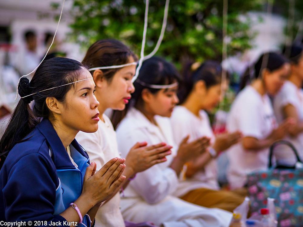 31 DECEMBER 2018 - BANGKOK, THAILAND: Women pray during New Year's Eve prayers and meditation at Wat Pathum Wanaram in central Bangkok. Many Thais go to temples to meditate and pray on New Year's Eve.    PHOTO BY JACK KURTZ