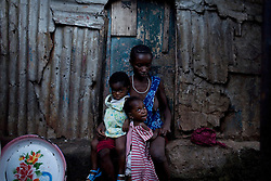 Fatu and her twin daughters, her and her family live in a slum in Freetown, forced to move there after her husband lost his job. Her daughters have struggled to put on weight and her husband is constantly sick. A few months after this photo was taken he died. Kroo Bay, Freetown, Sierra Leone.